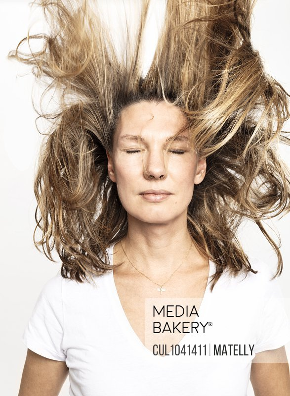 Woman with flying hair closing eyes, white background
