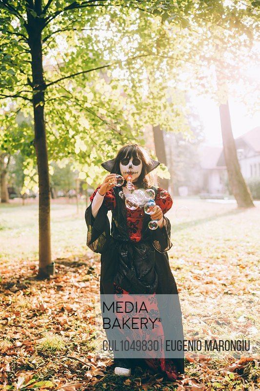 Girl in Halloween costume, blowing bubbles