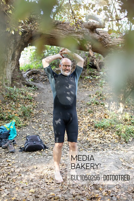 Man putting on wetsuit outside, Property Released (PR)eparing for swim