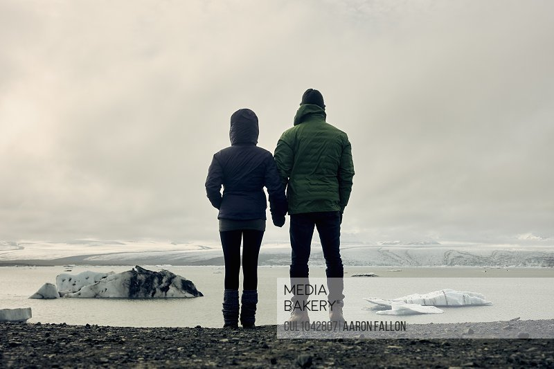 Silhouette of a couple standing on a beach and looking out to a sea with icebergs and snowy hills in the distance.