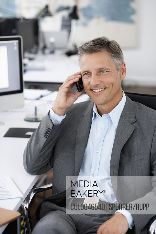 Man in office phoning