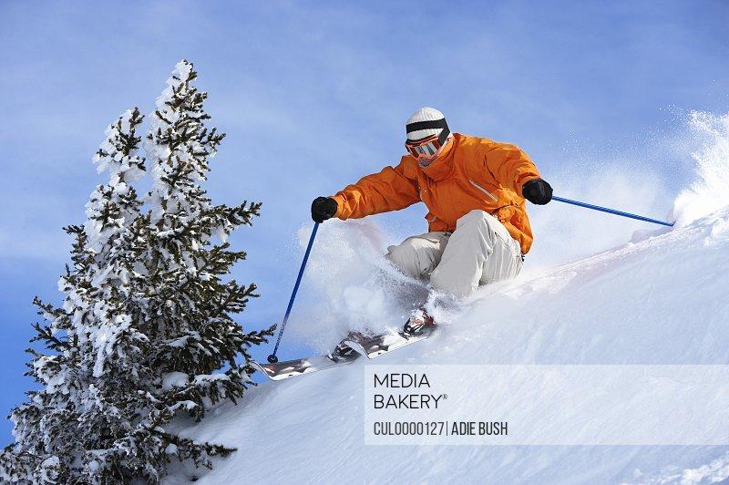man skiing over ridge on slope