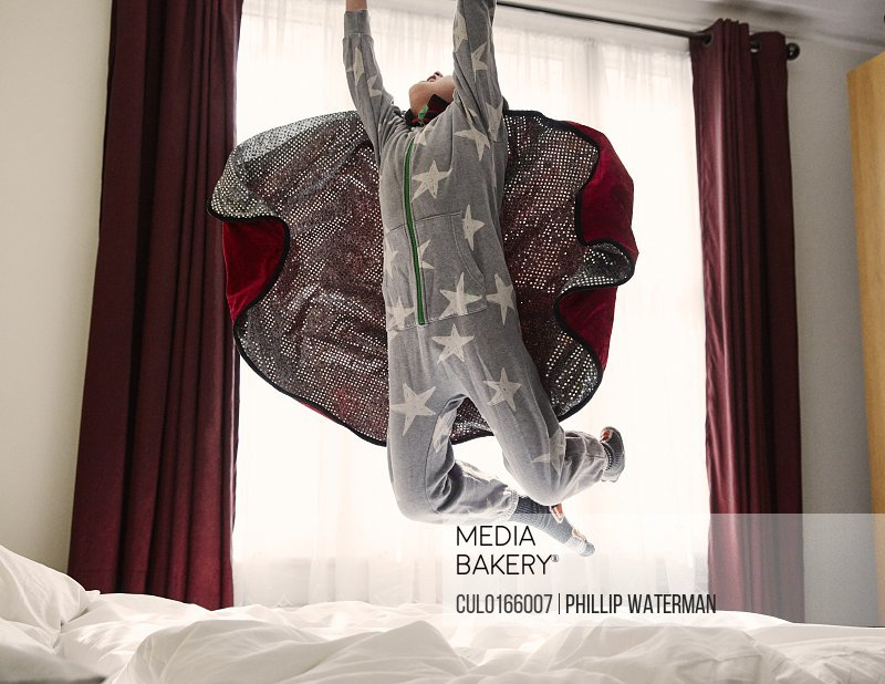 Young boy wearing cape jumping on bed