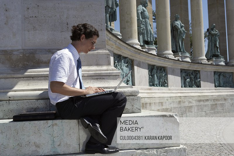 Businessman on laptop in Hero Square.