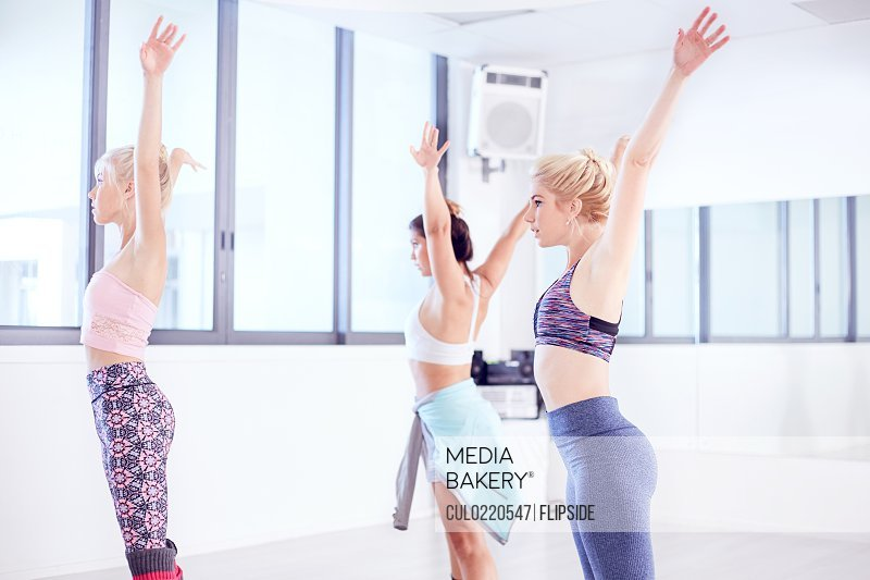 Female ballet dancers practicing with arms raised in dance studio