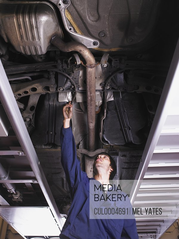 Mechanic standing under raised car