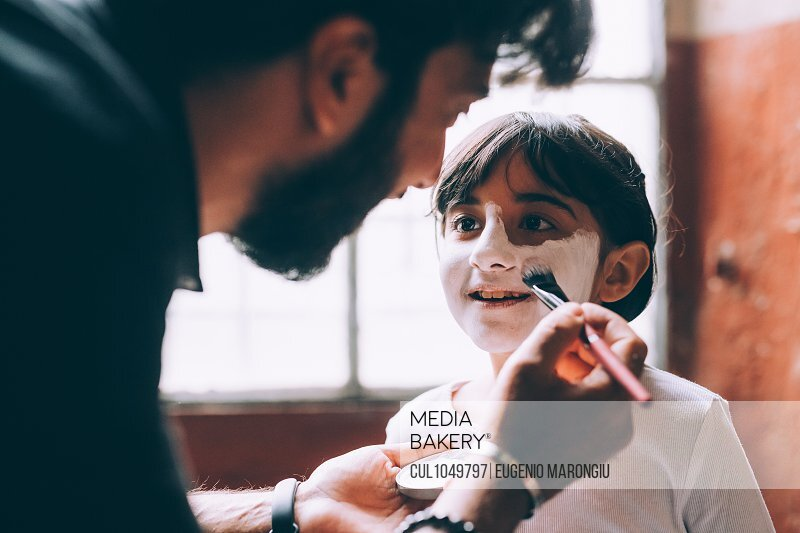 Father painting daughter's face for Halloween