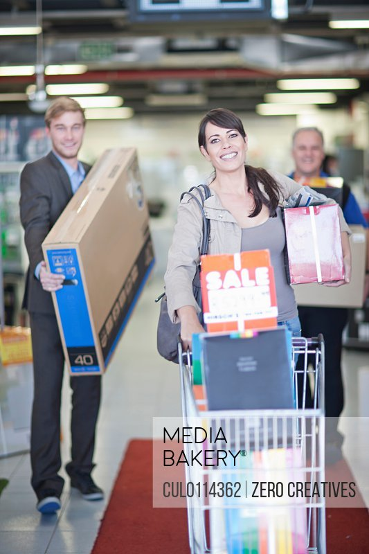 Woman leaving showroom with abundance of purchases/n
