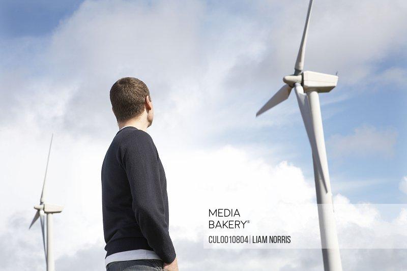 Man looking at wind turbines