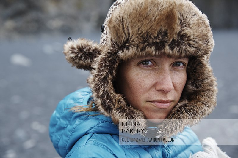 Woman wearing a fur lined hat and blue coat looking directly at the camera with a grey pebble beach in the background.