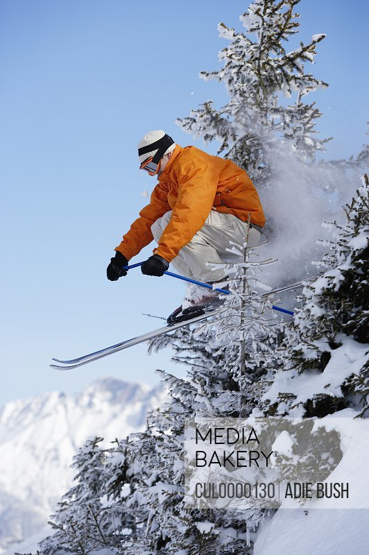 male skier jumping through trees on slope