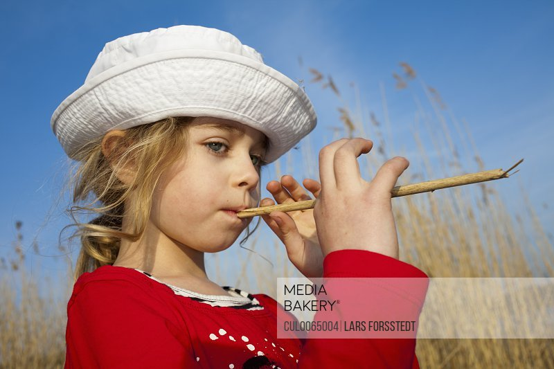 Toddler girl playing in wheat field