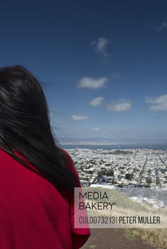Woman on hill overlooking cityscape