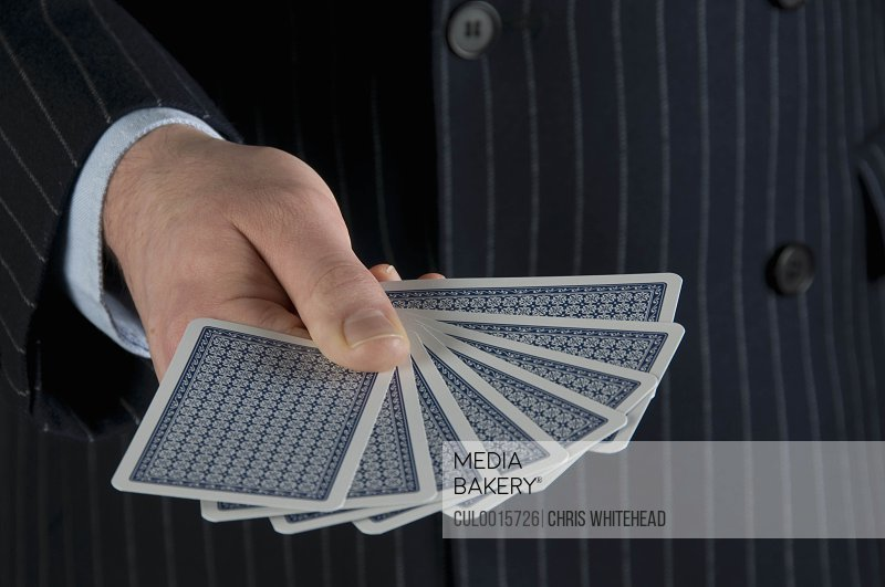 Male holding playing cards