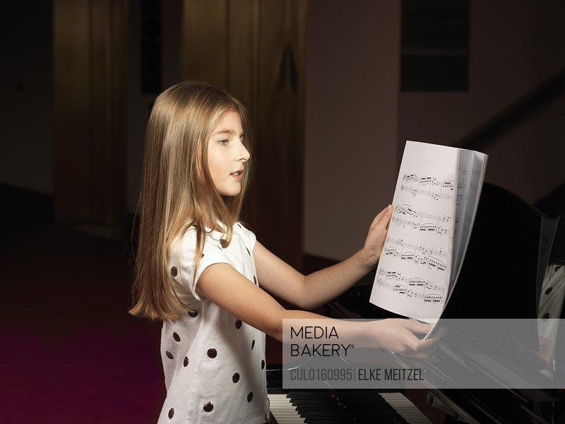 Girl choosing sheet music for piano