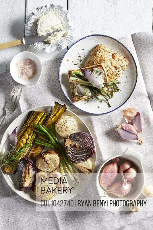 Plates and dishes with a variety of roasted garlic and onions, a selection of onions on toast, uncooked shallots in a bowl and a soft cheese in foil.