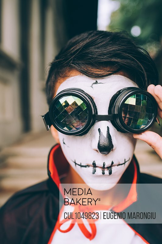 Boy wearing Halloween costume with face paint and goggles