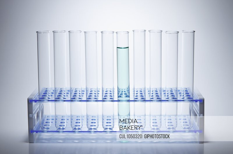 Test tubes in a rack, with one test tube containing green solution