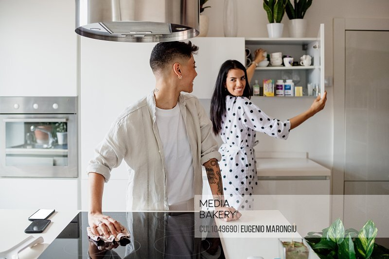 Young lesbian couple standing in kitchen, smiling at each other.