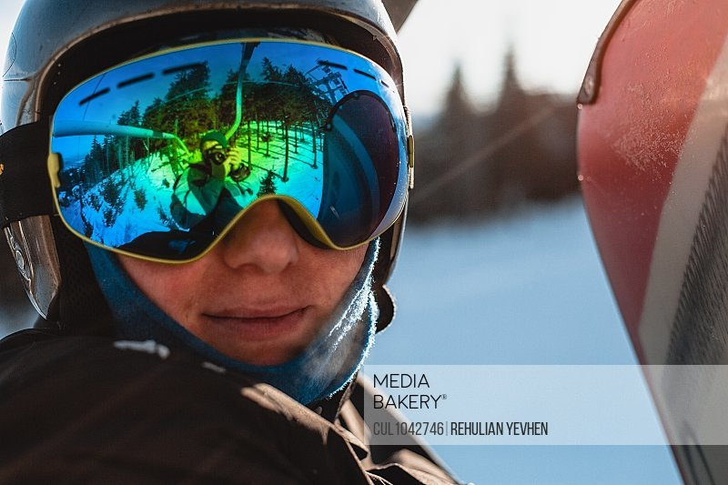 Head and shoulders of person wearing a black helmet and dark goggles on a ski slope.