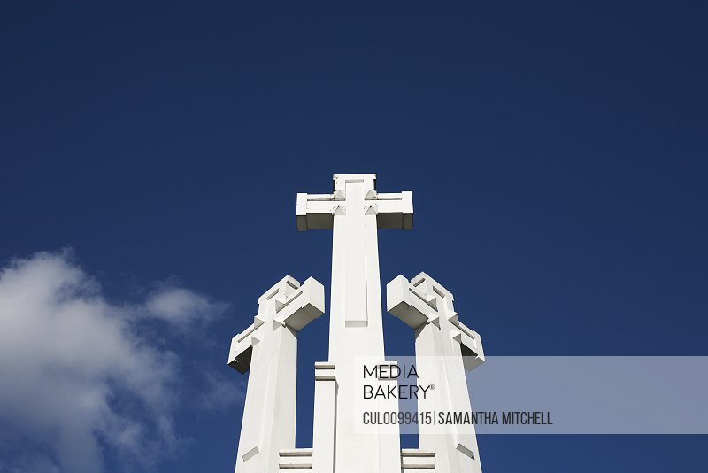 Low angle view of crosses blue sky