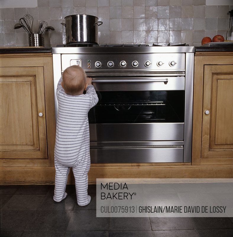Infant standing by oven in kitchen