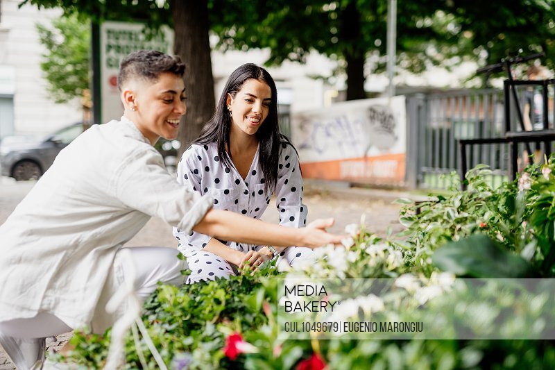 Young lesbian couple standing at market stall, looking at plants.