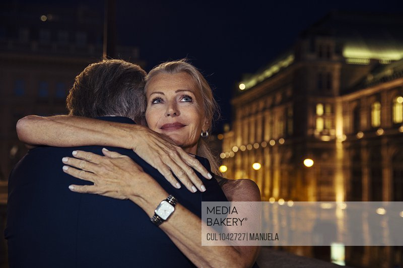 A woman hugging her partner and smiling over his shoulder during an evening out in Vienna.