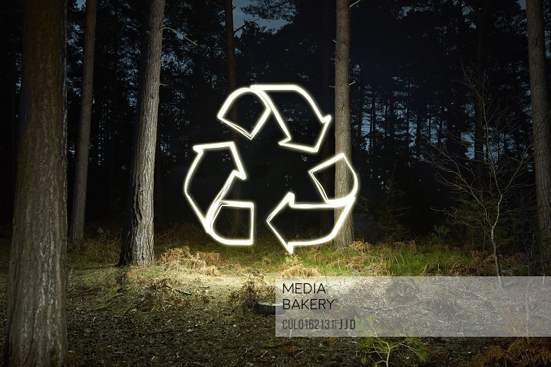 Glowing recycling symbol in forest at night