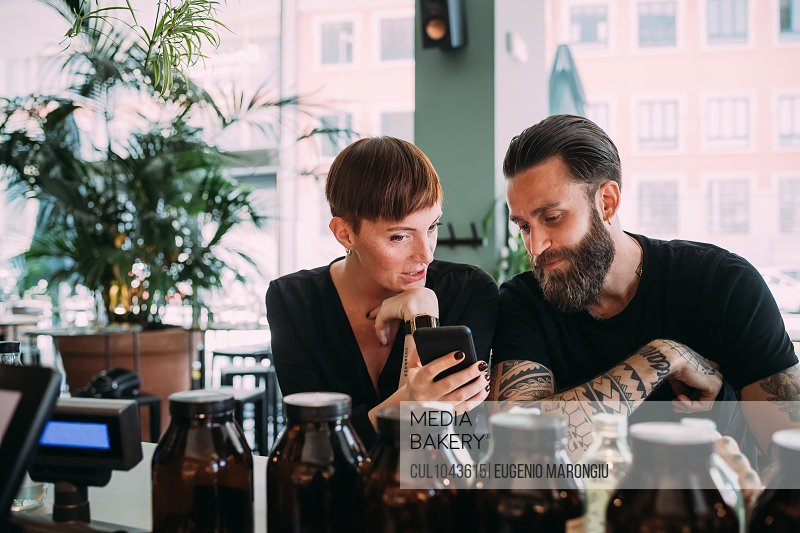 Bearded young man with brown hair and tattoos and young woman with short hair sitting in a bar, looking at mobile phone.