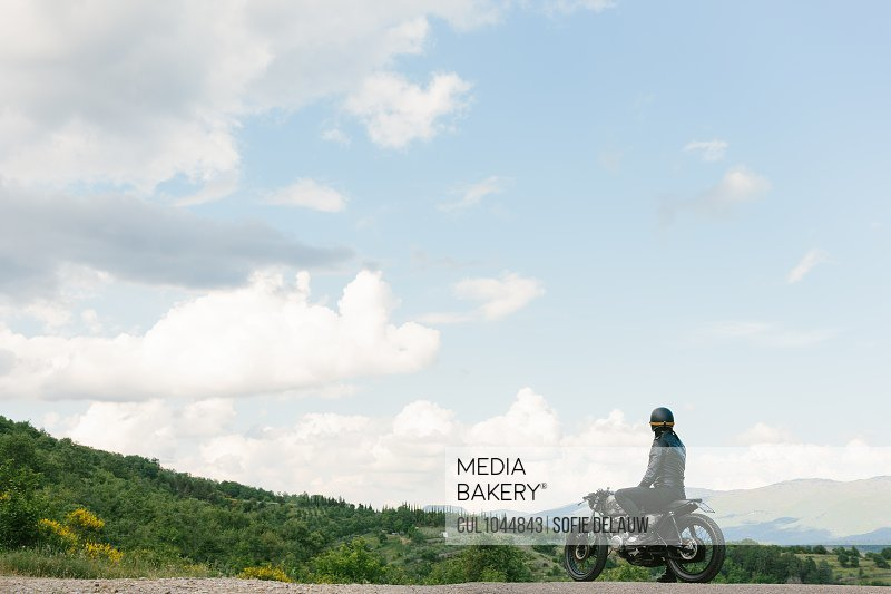 Young male motorcyclist on vintage motorcycle looking out over landscape, Florence, Tuscany, Italy