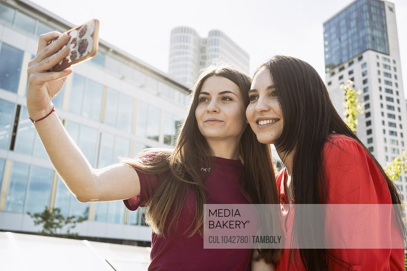 Two women standing in a city taking a selfie of themselves with a mobile phone