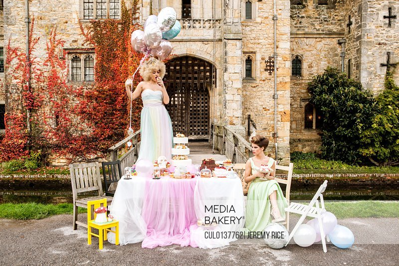 Bride standing on table bridesmaid sitting
