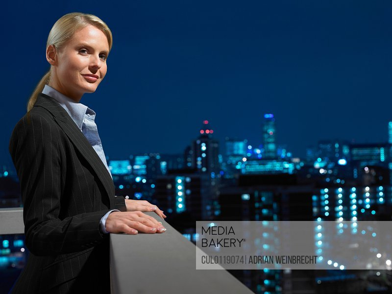 Smart lady in corporate environment overlooking the city/n