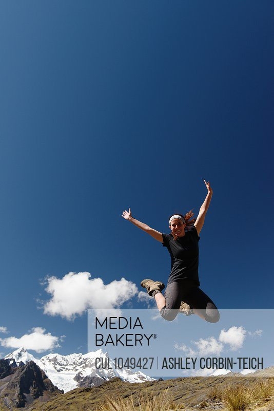 Young woman jumping against clear blue sky, Lares, Peru
