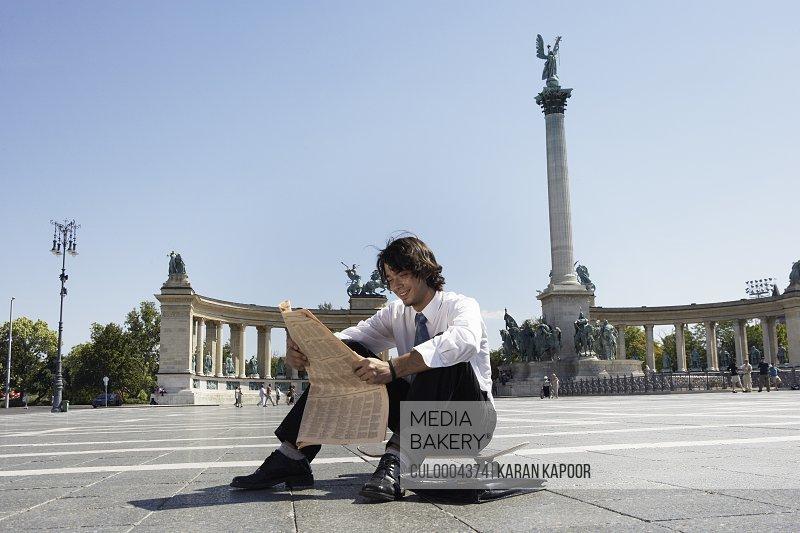Businessman reading newspaper in Hero Square.
