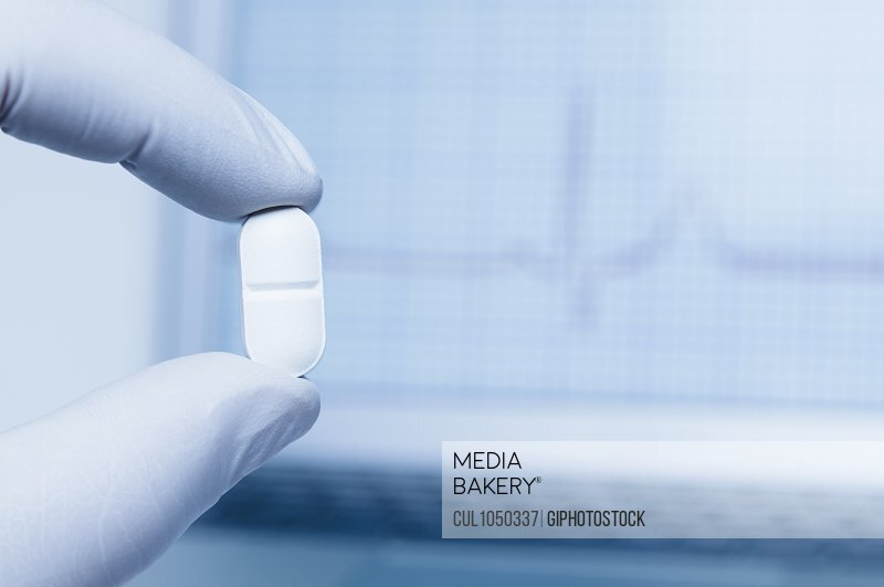 Hand holding a pill in front of a laptop computer displaying EKG trace