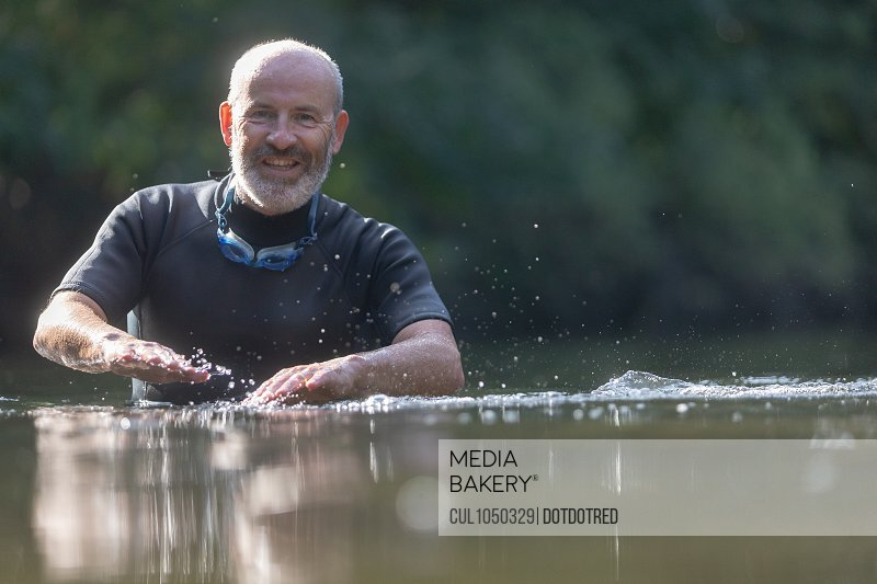 Swimmer in river, looking at camera and smiling
