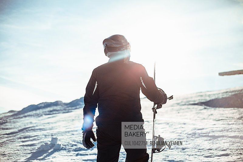 Silhouette of a person wearing a black ski suit, helmet and goggles holding a snowboard standing on top of a snowy slope.