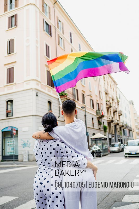 Rear view of young lesbian couple standing on a street, waving rainbow flag.