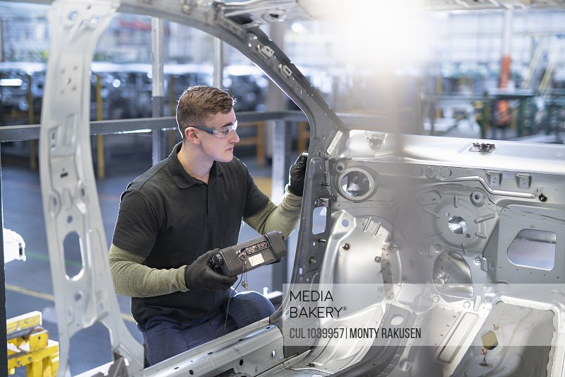 Engineer testing car body in car factory