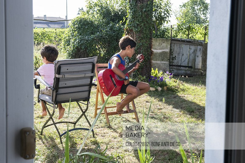 Two boys sitting on chairs in the garden, one playing a guitar.