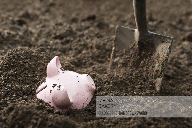 Shovel digging up piggy bank