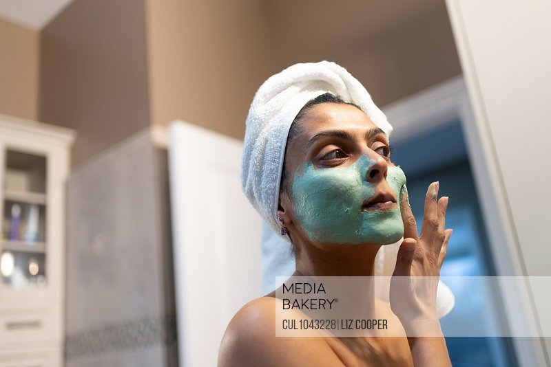 Woman standing in bathroom, applying face mask after bath.