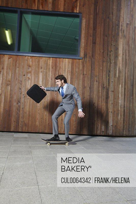 Businessman riding skateboard