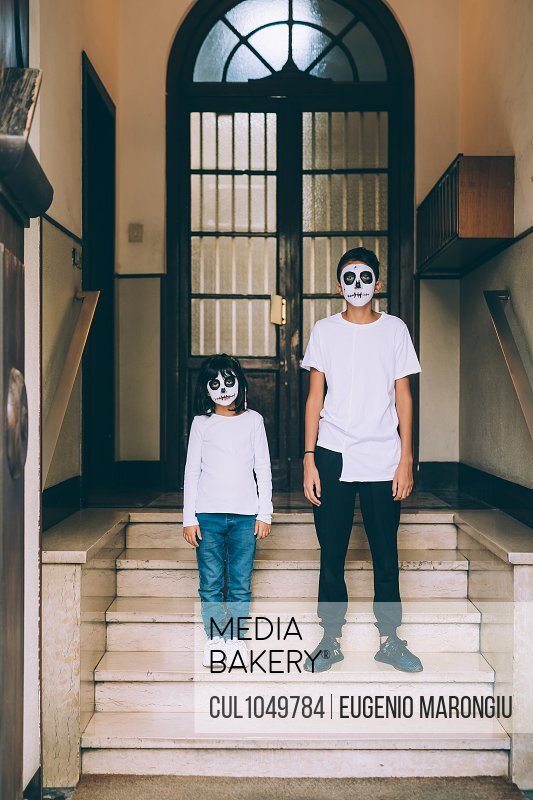 Sister and brother in Halloween face paint, standing on steps