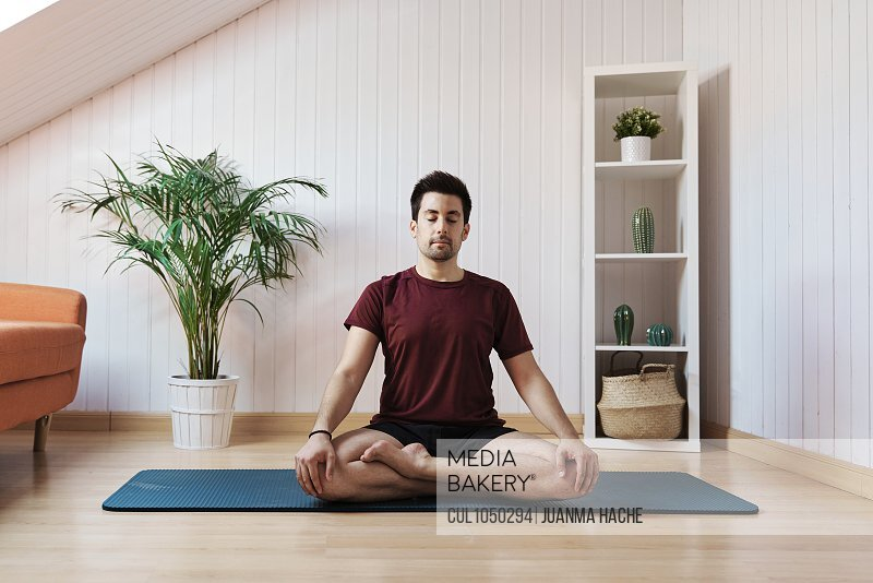 Man meditating at home, sitting with legs crossed
