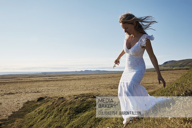 A woman wearing a long white dress on a grassy bank to the beach