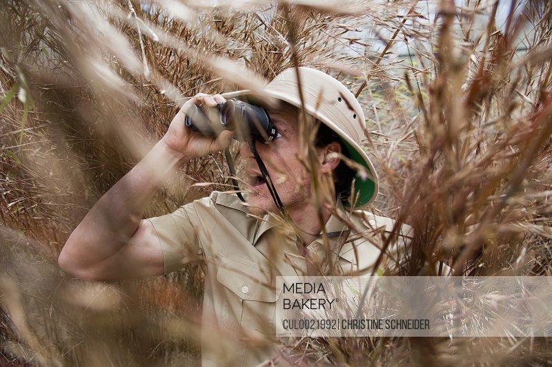 man in jungle outfit using binoculars