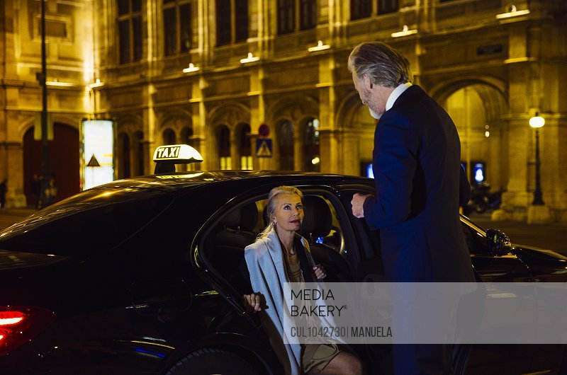 A man holding open a taxi door for a woman in a Vienna street.
